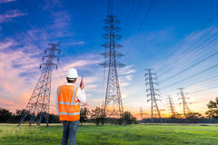 Electrical engineer with high voltage electricity pylon at sunri. Se background Stock Photography