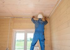 Electrical engineer performs installation of electrical wiring. In a new wooden country house stock photo