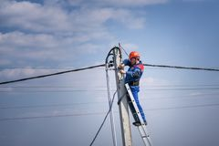 Electrical engineer performs wiring on a high pole standing on the stairs. high-rise electrical work. podkluchenie house to the. Power lines royalty free stock photos