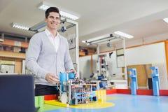 Electrical engineer programming a robot during robotics class Stock Photos
