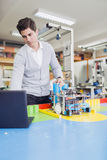 Electrical engineer programming a robot during robotics class royalty free stock image