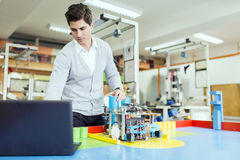 Electrical engineer programming a robot during robotics class. Male electrical engineer programming a robot during robotics class Stock Photography