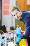 Electrical engineer programming a robot during robotics class Royalty Free Stock Images
