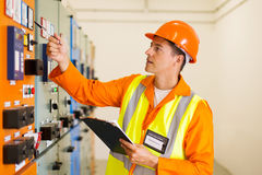Electrical engineer. Successful electrical engineer writing down machine setting data Stock Image