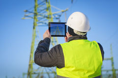 Electrical Engineer with tablet PC. Near High voltage tower Stock Image