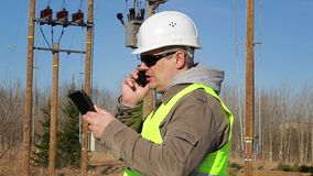 Electrical engineer with tablet PC talking on cell phone stock video footage