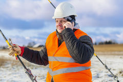 Electrical Engineer talking on cell phone near tensioner Royalty Free Stock Photos