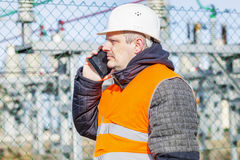 Electrical engineer talking on cell phone at power station Royalty Free Stock Photos
