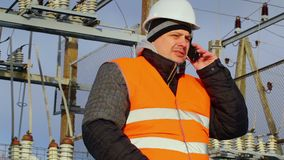 Electrical Engineer talking on cell phone in substation stock video