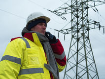 Electrical engineer Talking on the phone power grids on the background Stock Photography