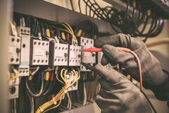 Free Electrical Engineer Using Digital Multi-meter Measuring Equipment To Checking Electric Current Voltage At Circuit Breaker Royalty Free Stock Photo - 191665375