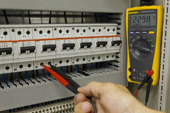 Electrical engineer at work. Electrical engineer measuring voltage on a miniature circuit breaker stock photography