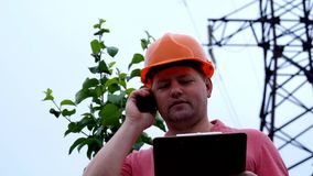 Electrical engineer working. Talking on the phone and working on the tablet. Checking the power grids stock video footage