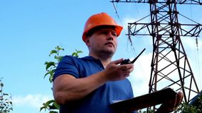 Electrical engineer working. Talking on the phone and working on the tablet. Checking the power grids stock footage