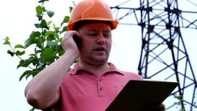 Electrical engineer working. Talking on the phone and working on the tablet. Checking the power grids stock video