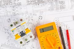 Electrical engineering drawings, modular circuit breaker and digital multimeter. royalty free stock photos