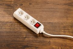 Electrical extension block or power strip on floor. Electricity at home. White electric power strip or extension cord block for extending plug with red switch on Royalty Free Stock Photos