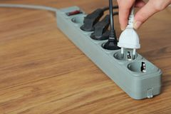Electrical extension cord. With electric plug on the wooden floor. Concept of energy saving Stock Photos