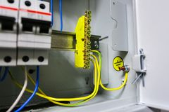 Electrical ground wires is connected to ground copper bar or earth bonding bar in metal electric breaker box with. Electrical yellow green ground wires is Stock Photo