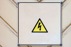 Electrical hazard sighn on wooden light yellow background. Stock Images