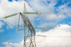 Electrical high volatge power line tower pillar on meadow hill area in front of blue sky and clouds stock images