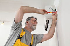 Electrical installation of air conditioner, electrician at work. Electrician installing electrical plug for air conditioner Stock Photos
