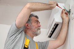 Electrical installation of air conditioner, electrician at work. Electrician installing electrical plug for air conditioner Royalty Free Stock Photo