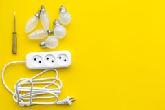 Electrical installation, wiring works. Bulbs and socket outlet on yellow background top view copy space. Electrical installation, wiring works. Bulbs and socket royalty free stock photos