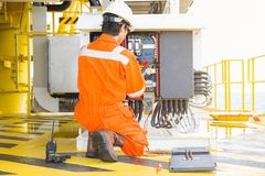 Electrical and instrument worker inspect and checking voltage and current of electric system at oil and gas platform for preventiv royalty free stock images
