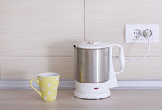 Electrical kettle and teacup Stock Photos