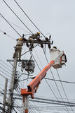 An electrical lineman working on a line Stock Image