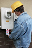 Electrical lock out. Electrician places a lock out tag on an electrical panel Stock Photography