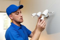 Electrical maintenance - electrician change light bulb. In wall lamp Stock Photography