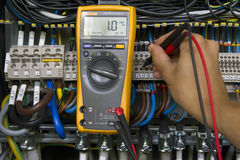 Electrical measurements. Electrician performing voltage measurements with electrical multimeter royalty free stock photography