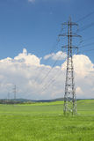Electrical net of poles on a green mead. Electrical net of poles on a panorama of blue sky and green meadow Royalty Free Stock Photography