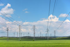 Electrical net of poles on a meadow. Electrical net of poles on a panorama of blue sky and green meadow Stock Photos