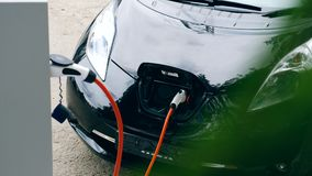 Electrical nozzle is inserted into an electrocar. 4K stock footage