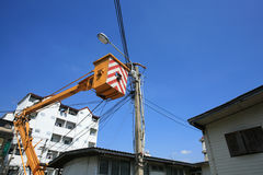Electrical officer on yellow crane installing lamp. Post Royalty Free Stock Photos