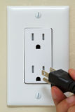 Electrical Outlet. Electric cable on the hand and Electrical Outlet on the Wall. Power 110v stock photos