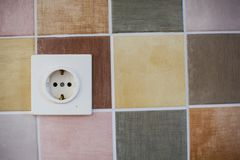 Electrical outlet. On the wall with colored tiles royalty free stock photo