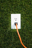 Electrical outlet in grass. With extension cord plugged in Royalty Free Stock Photography