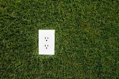 Electrical outlet in grass. Alternative energy source Stock Photo
