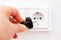 Electrical outlet with plug. Electrical outlet with hand and power plug royalty free stock photos