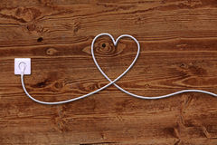 Electrical outlet and wire on wooden surface Royalty Free Stock Photography