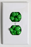 Electrical plate with green candy. Electrical power plate with green energy candy inside Royalty Free Stock Photos