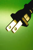 Electrical plug against green background Royalty Free Stock Images