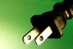 Electrical plug against green background Stock Photos