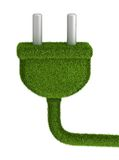 Electrical plug covered by green grass Royalty Free Stock Images