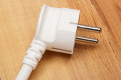 Electrical plug on wooden floor Stock Image