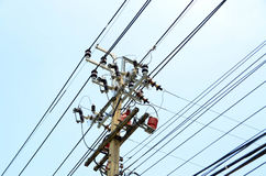 Electrical pole with power lines against hazy blue sky Royalty Free Stock Images